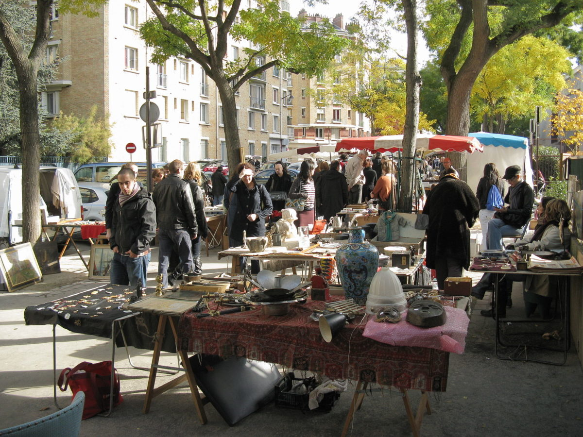 a crowd of people gathered around tables selling various wares in a park