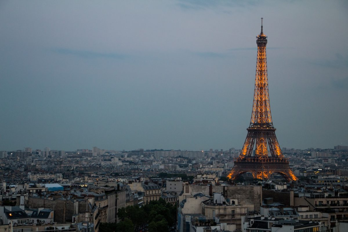 a overcast sky over Paris with the lit-up Eiffel Tower in the distance