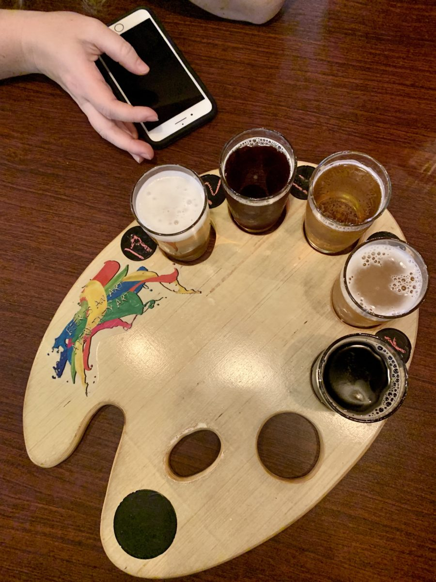 several small glasses of beer served on an artist palette