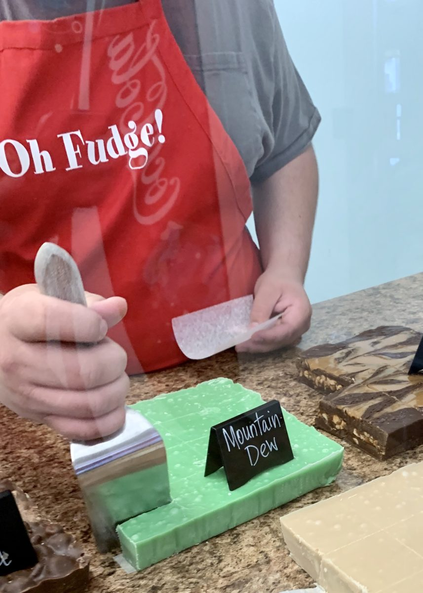 "bright green Mountain Dew fugdge being portioned by store worker in a red apron that says, ""Oh, Fudge!"""