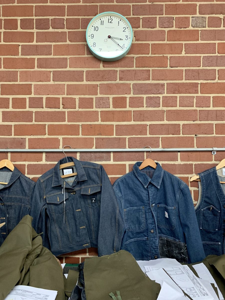 a clock and denim workman jackets against a brick wall