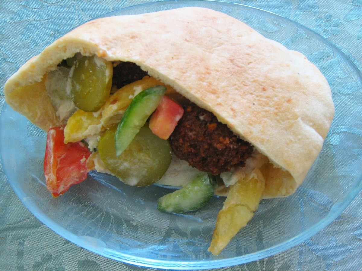 a pita pocket stuffed with falafel and greens