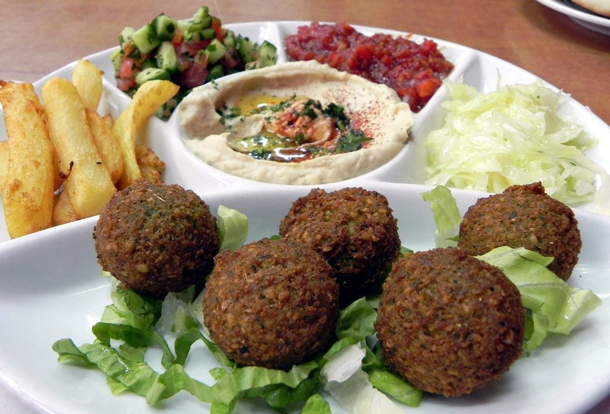a white plate stacked with falafel, hummus, and various dips