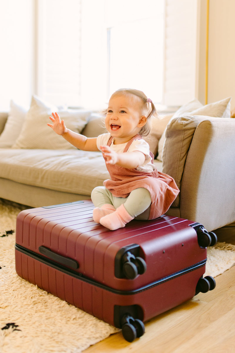 a baby sits on top of a dark red suitcase with a playful expression