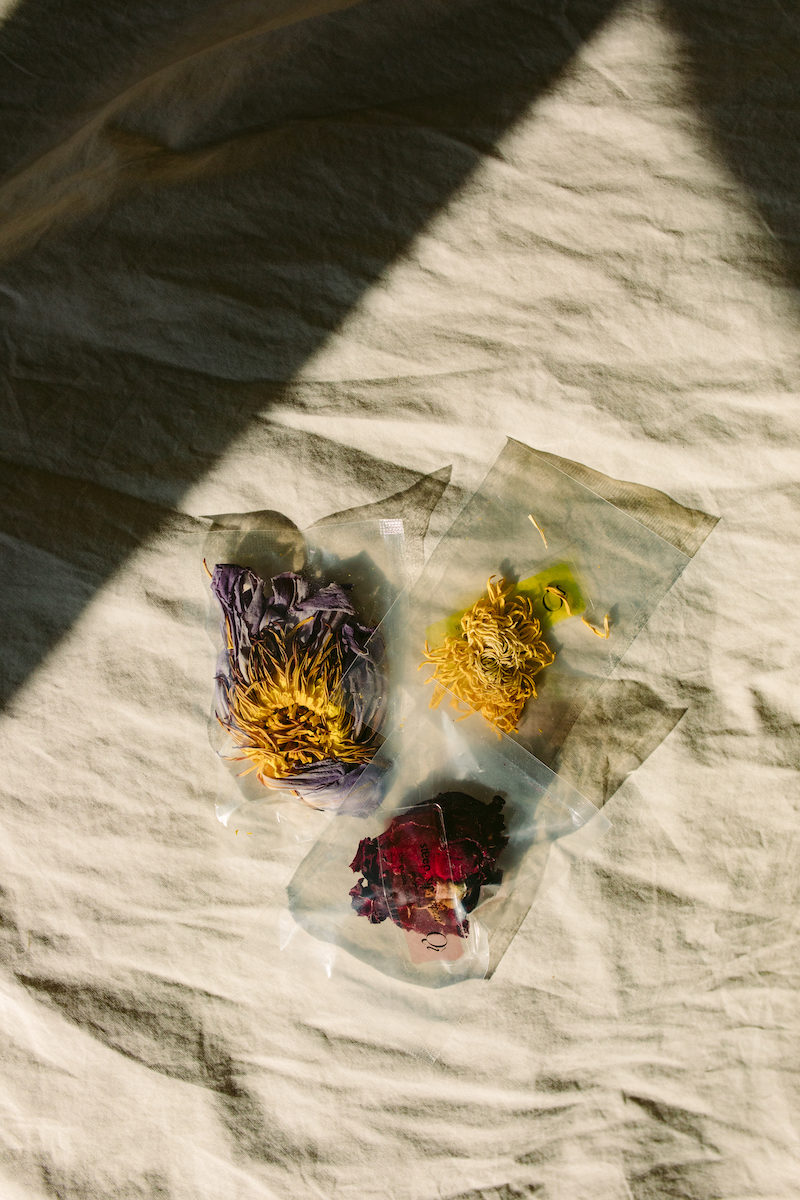 packets of floral tees on a bed