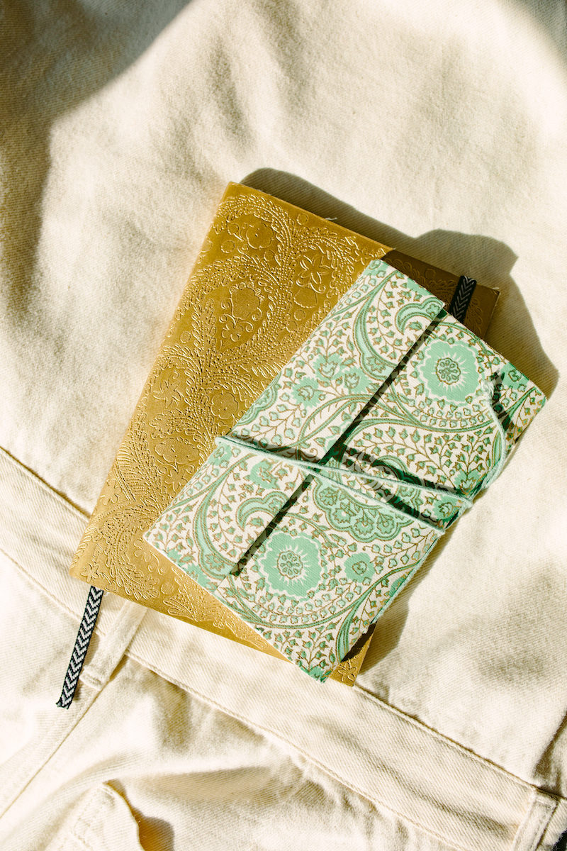 turquoise and gold silk-bound journals on a bed