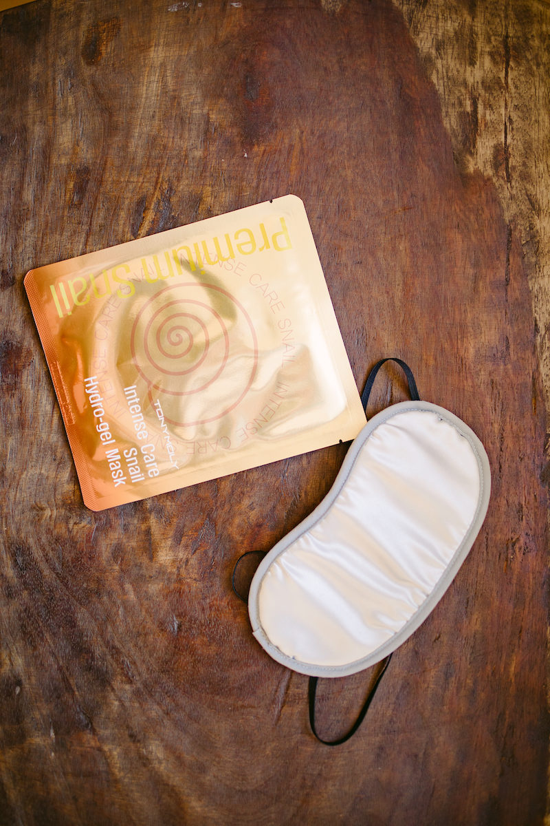 a white sleep mask and sheet mask packet on wood