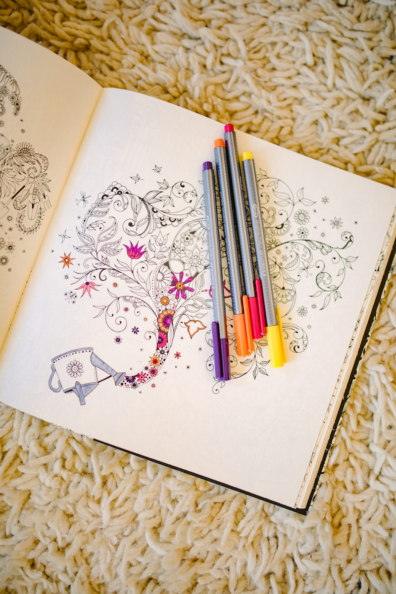 a half-filled coloring book page with pens