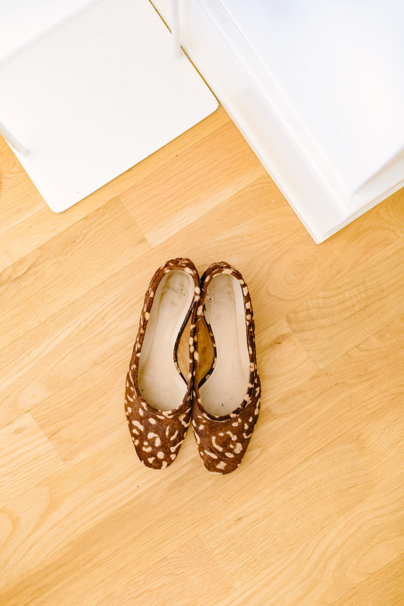 a pair of leopard print ballet flats on a wooden floor