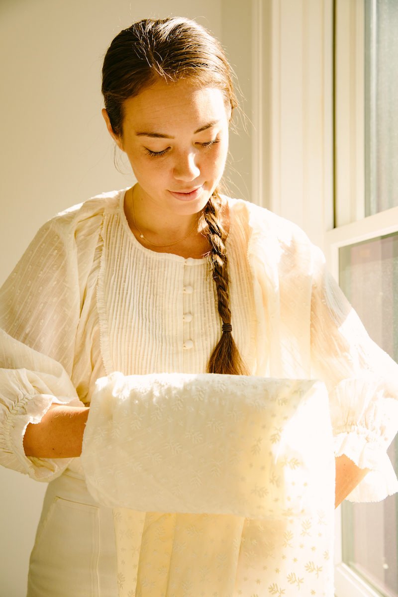 a woman folding white linen fabric as sun pours in through the window