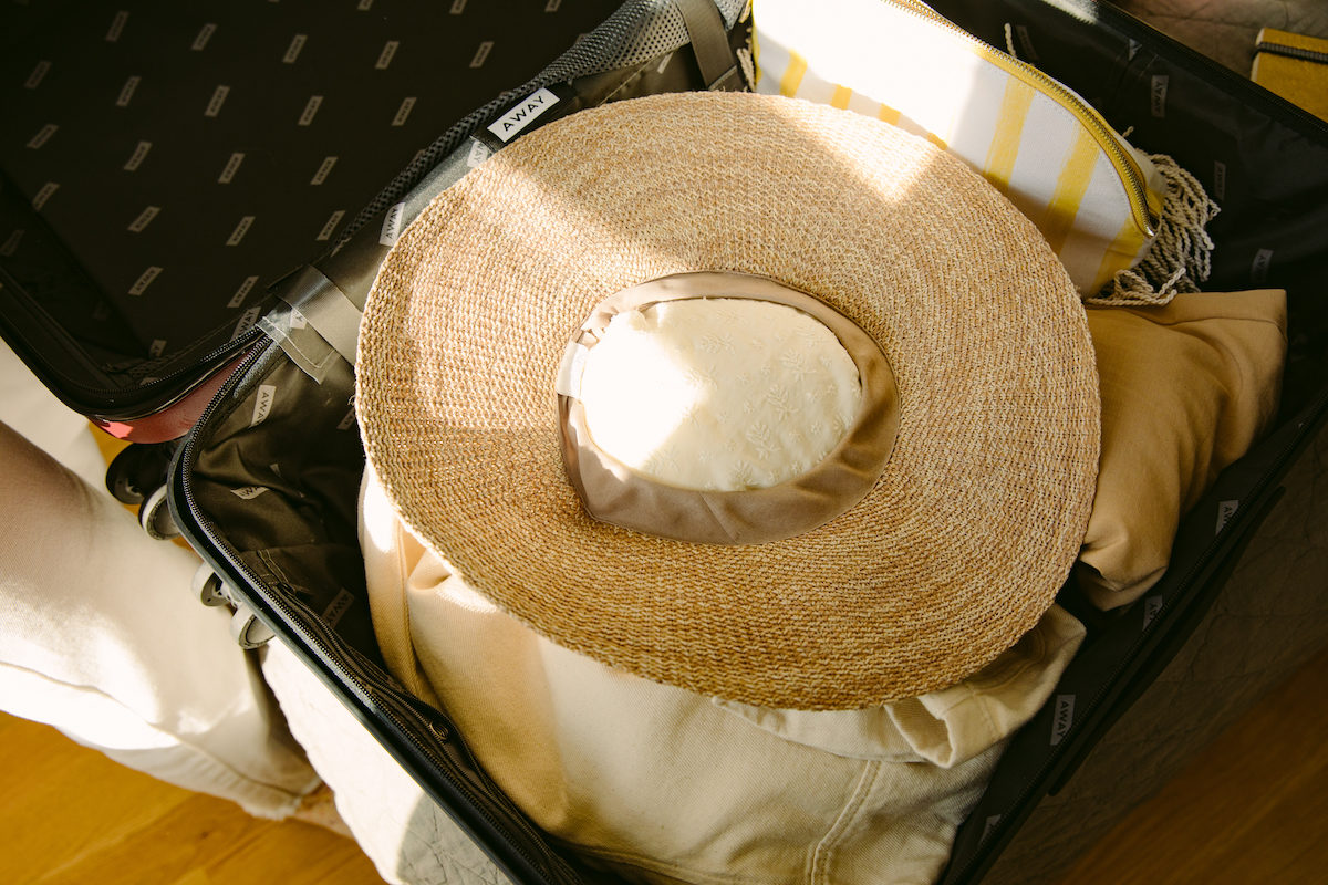 a brimmed straw hat packed in a suitcase with fabric stuffing the head