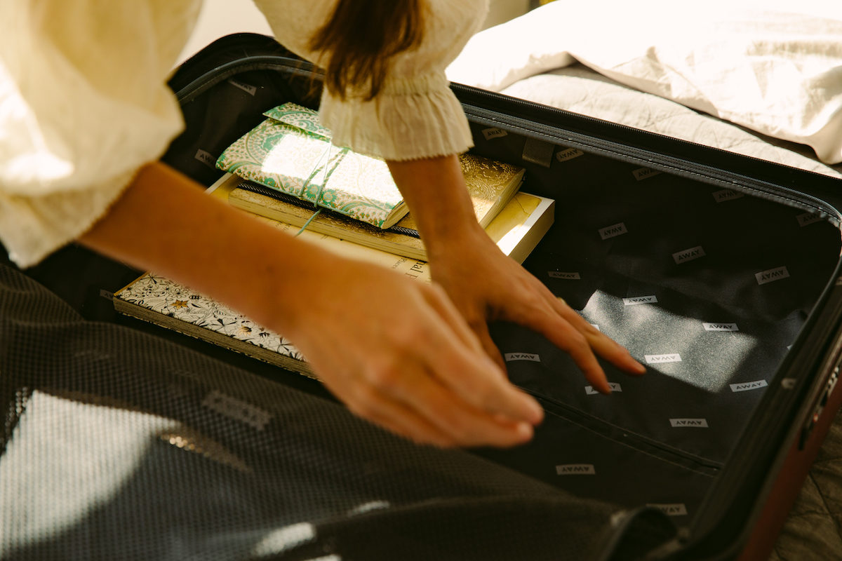 a pair of woman's hands move things around in a suitcase