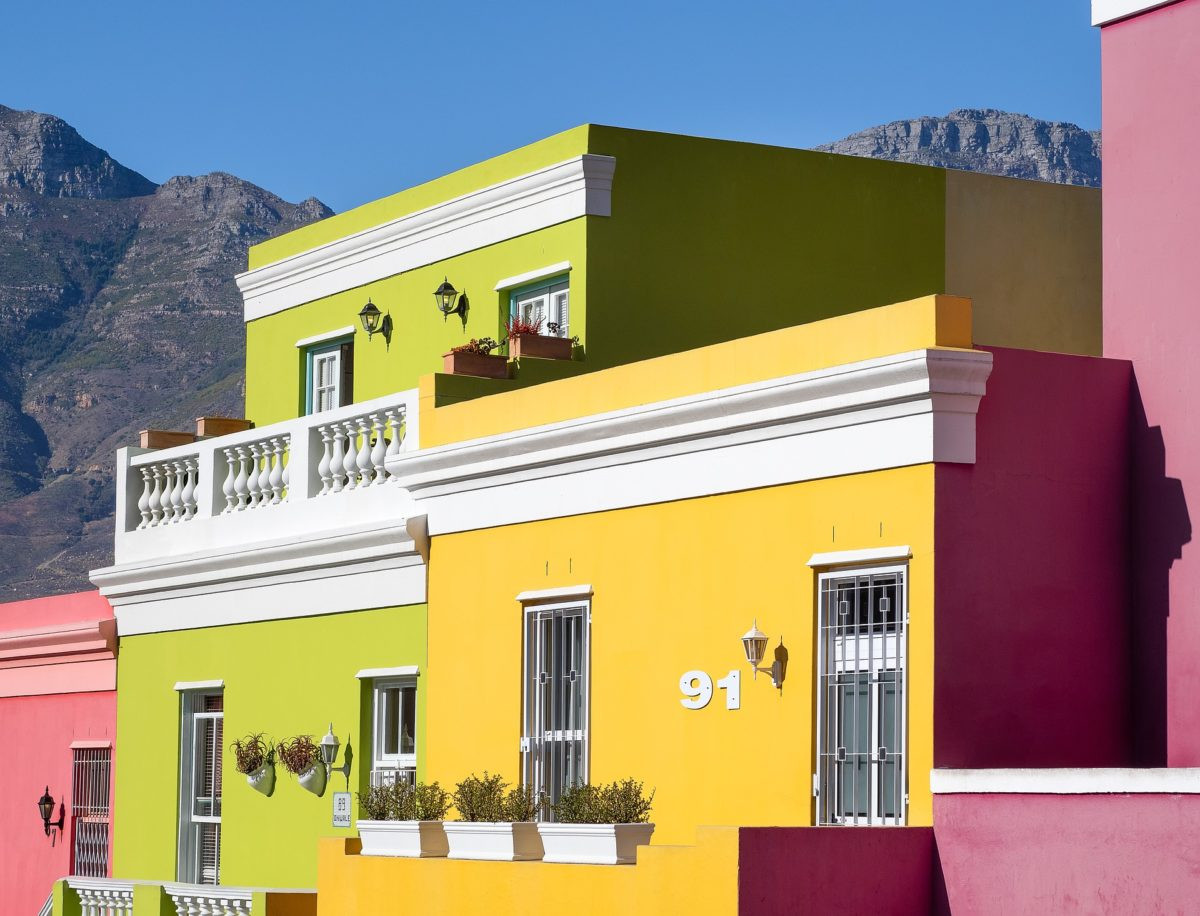 green, yellow, and pink houses with mountain in the background