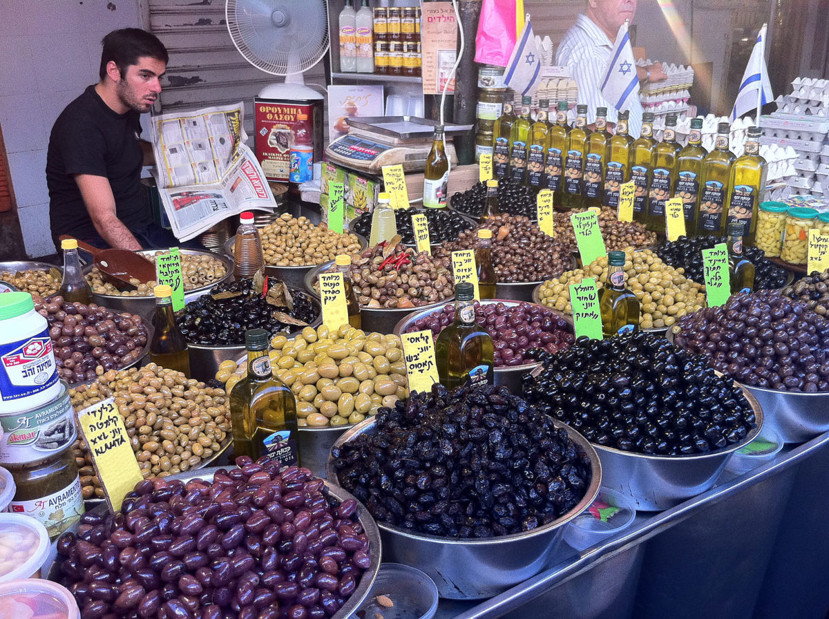 a man working at a booth selling large barrels of olives