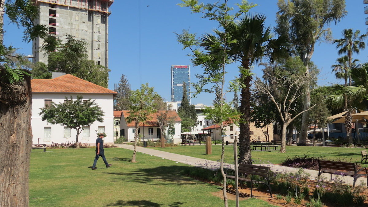 a man walking through small park with several villas and a skyscraper in the distance