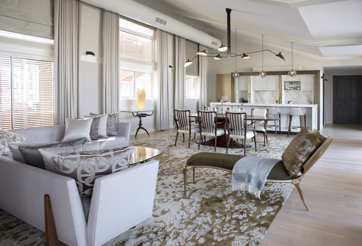 a luxurious white room filled with plush white chairs, couches, rugs, and other furnishings