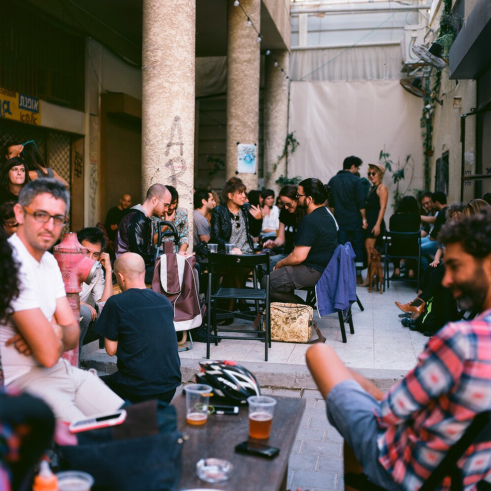 several groups of people sitting and talking at tables while drinking beers