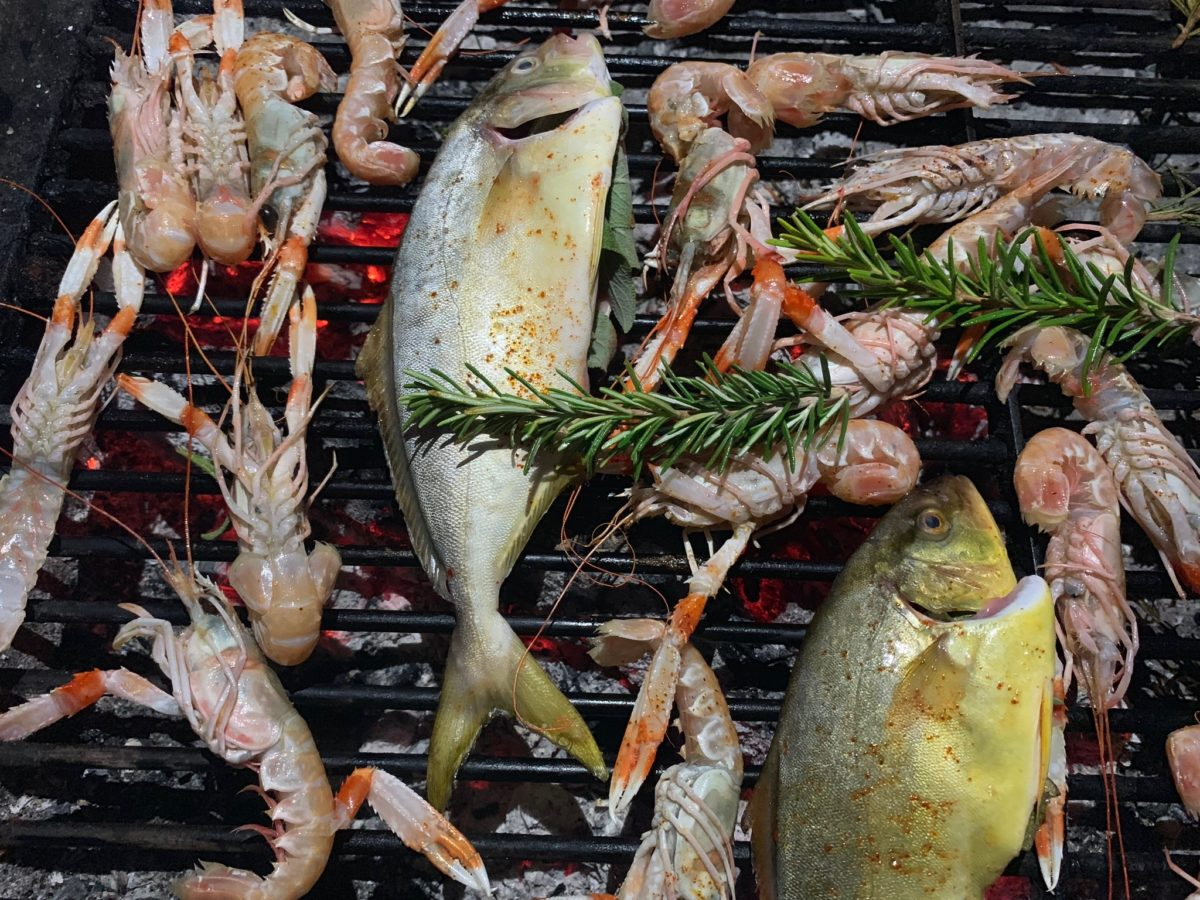 whole fish and herbs on a grill