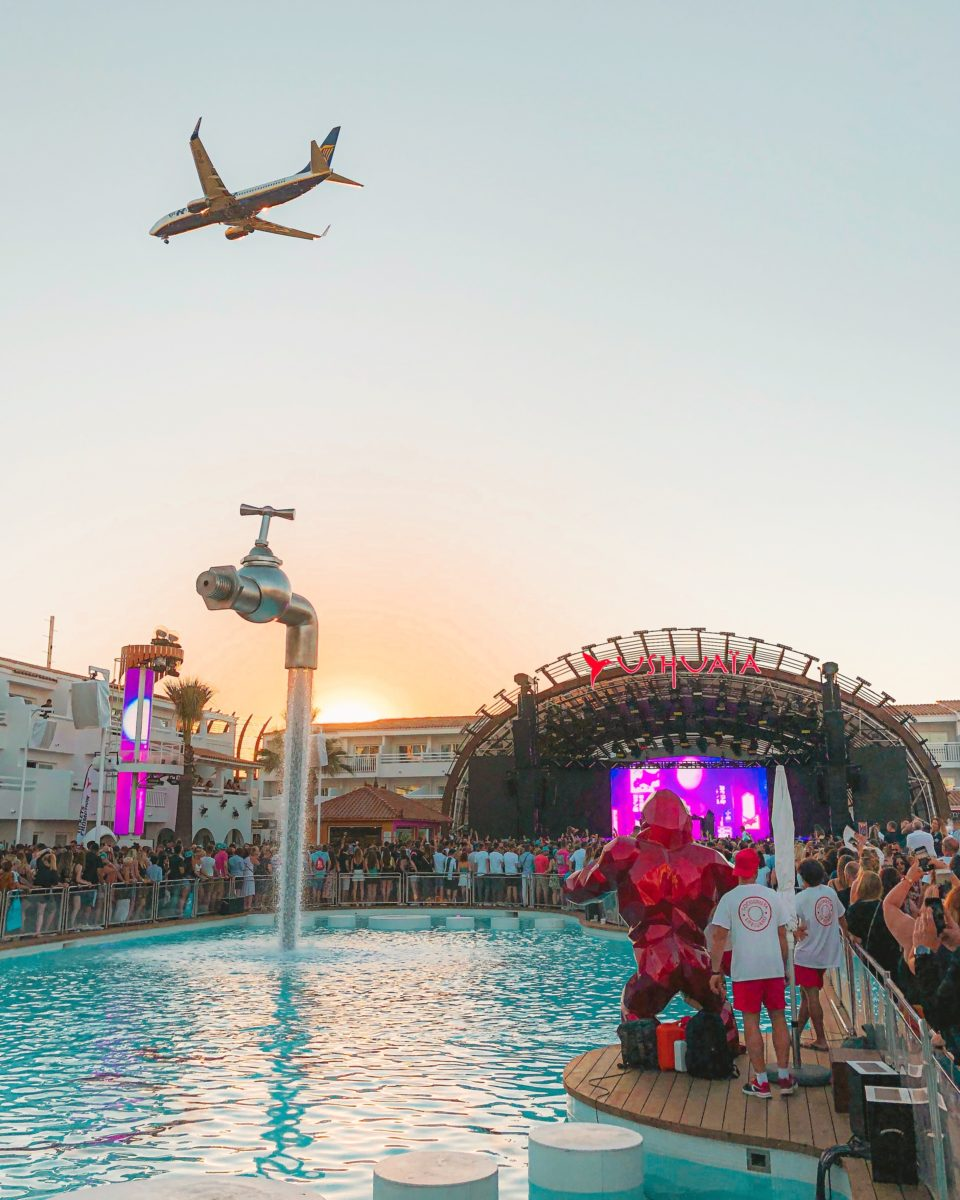 a plane soaring over an open-air club with a large pool and purple-lit stage