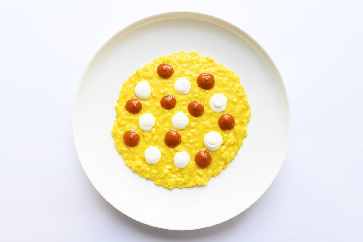bright yellow risotto dish with dots of red and white