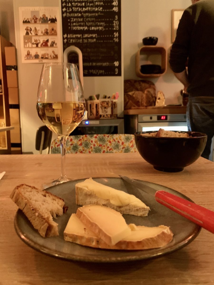 plate of cheese with glass of white wine on table