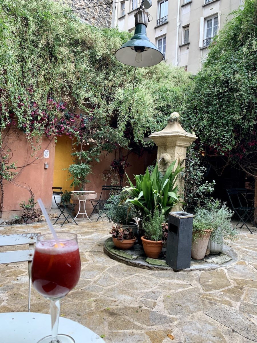 red cocktail in a courtyard with fountain and greenery