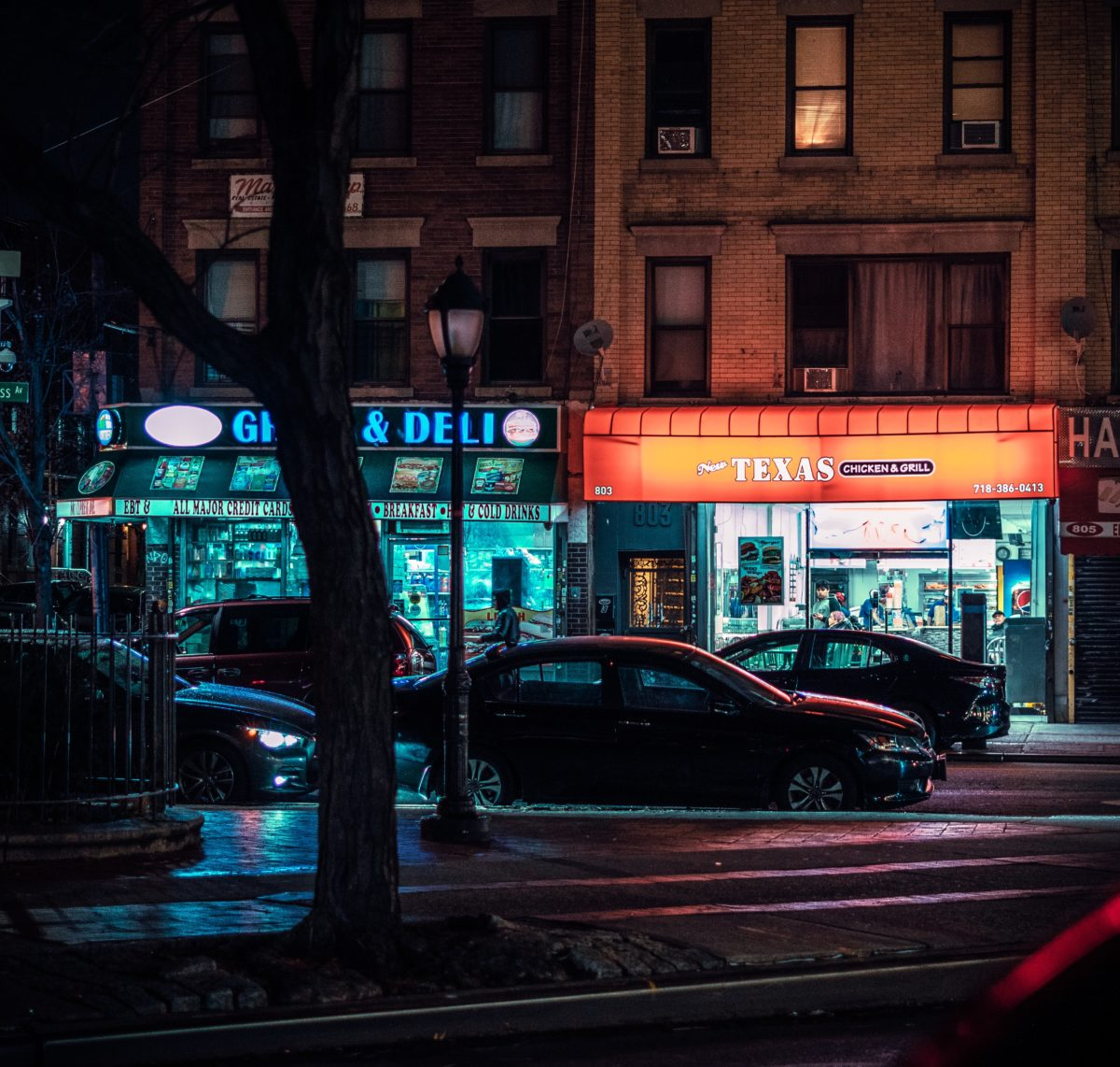 two store fronts lit by their signs at night