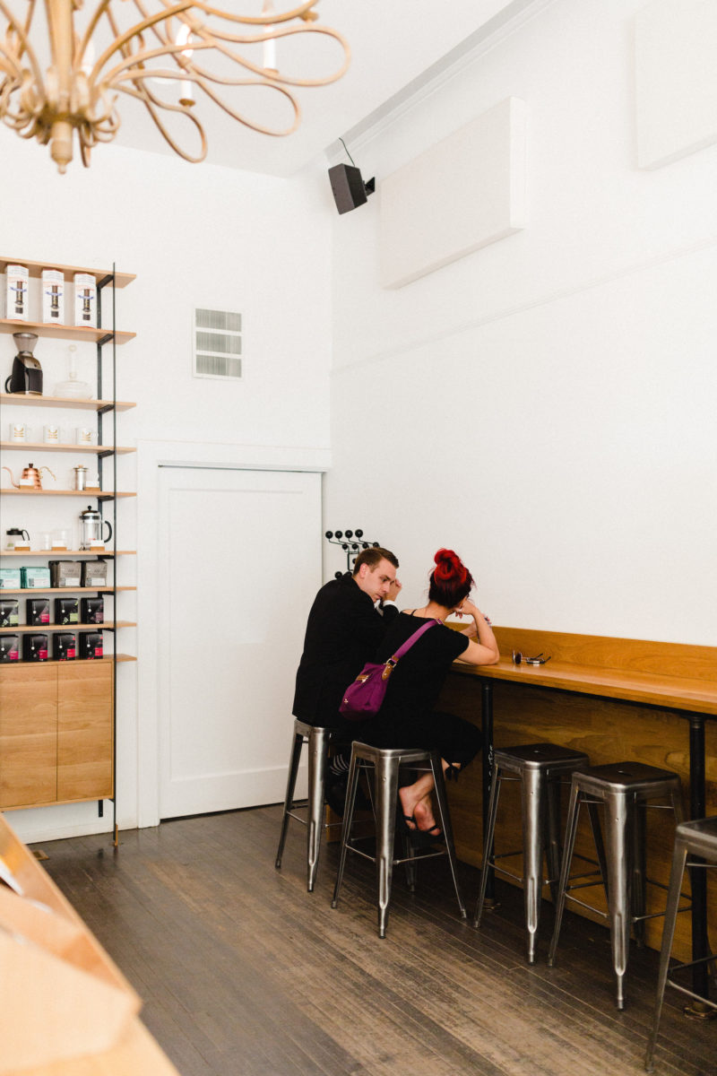 two people sitting at a counter in a coffee shop