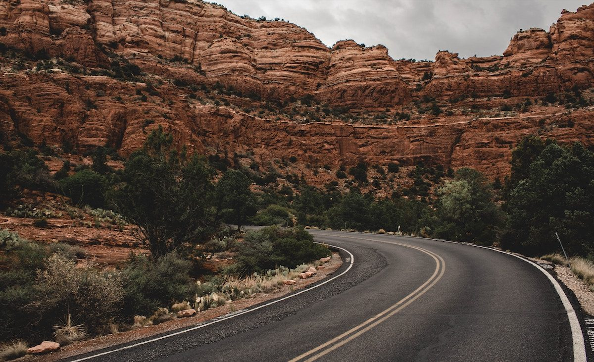 high way curving through tall red rock formations