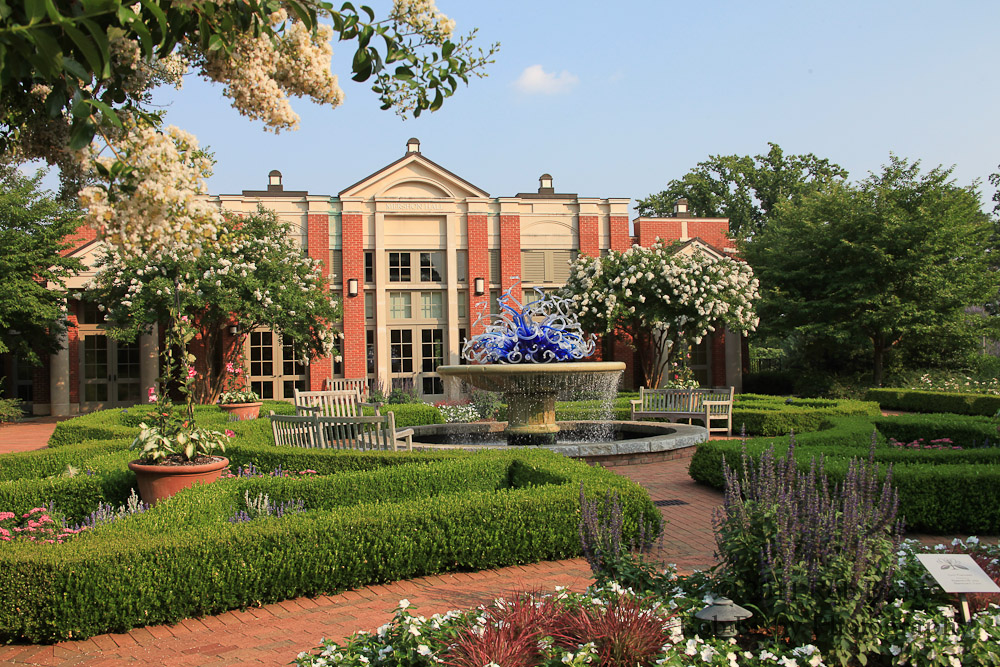 a building sitting in the middle of plaza with a fountain, hedges, a glass sculpture, and flowers