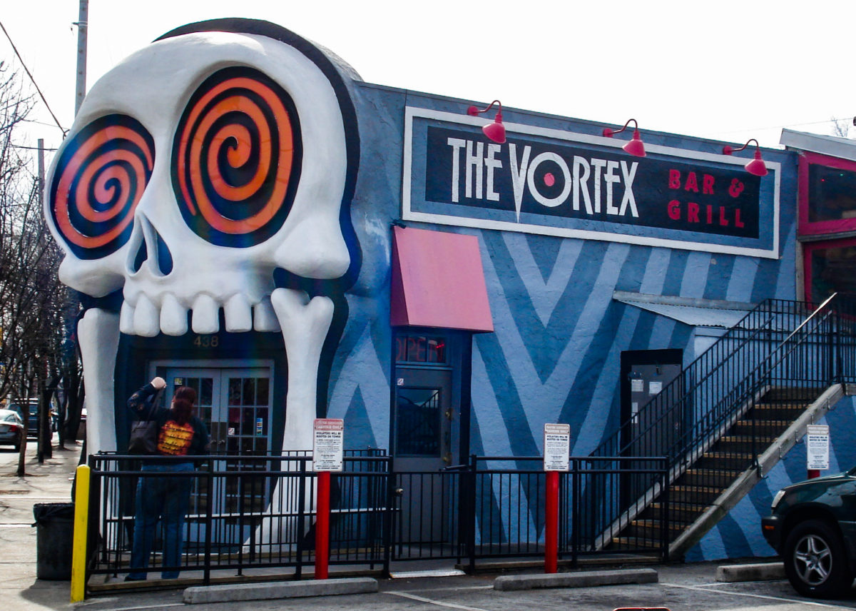 a blue building with a giant skull with swirling eyes as a door