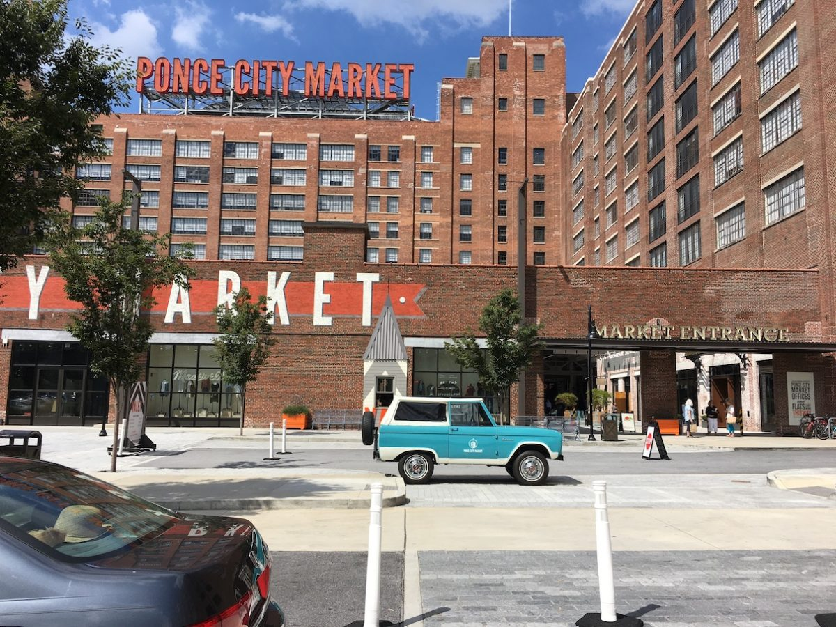 a multi-story brick building with a sign reading Ponce City Market on a sunny day