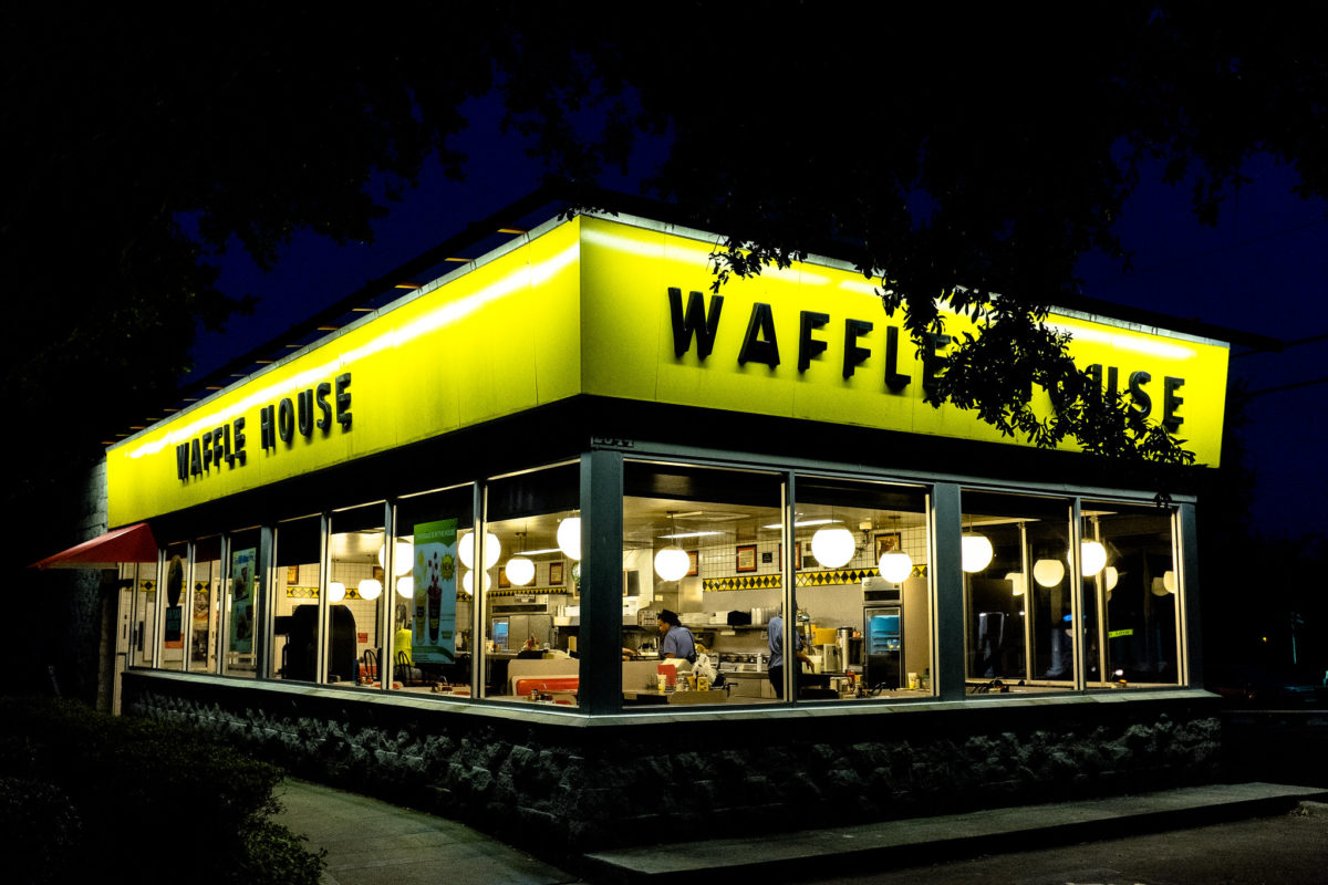a glowing waffle house at night