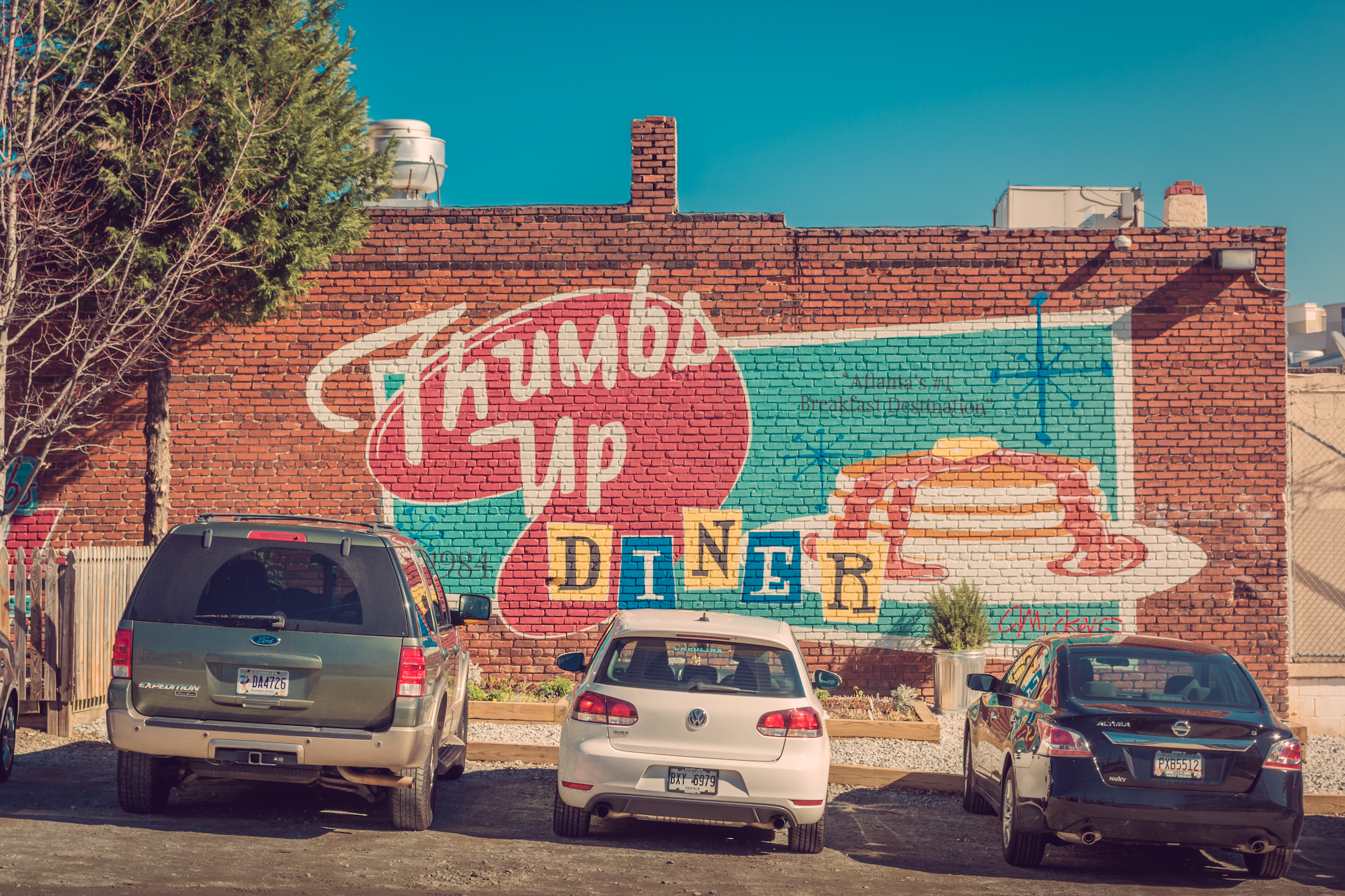 cars parked in front of a 50s style wall mural reading Thumbs Up Diner