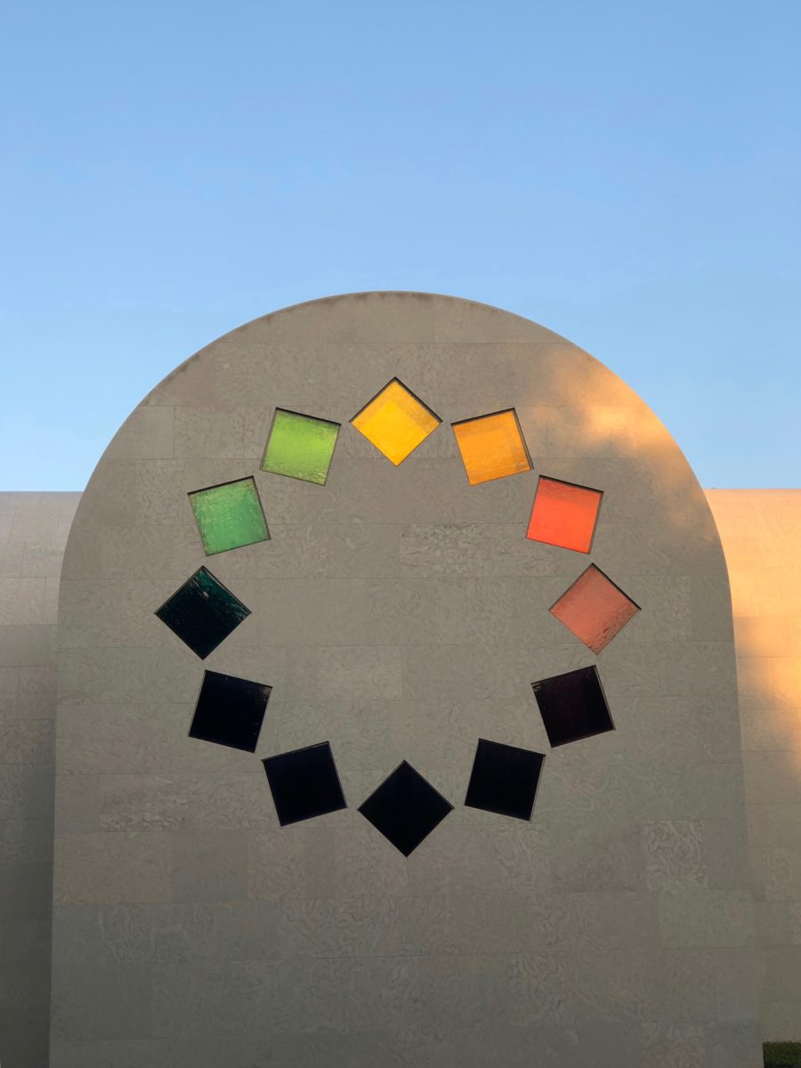 circle of square windows in each color of the rainbow on chapel-like building