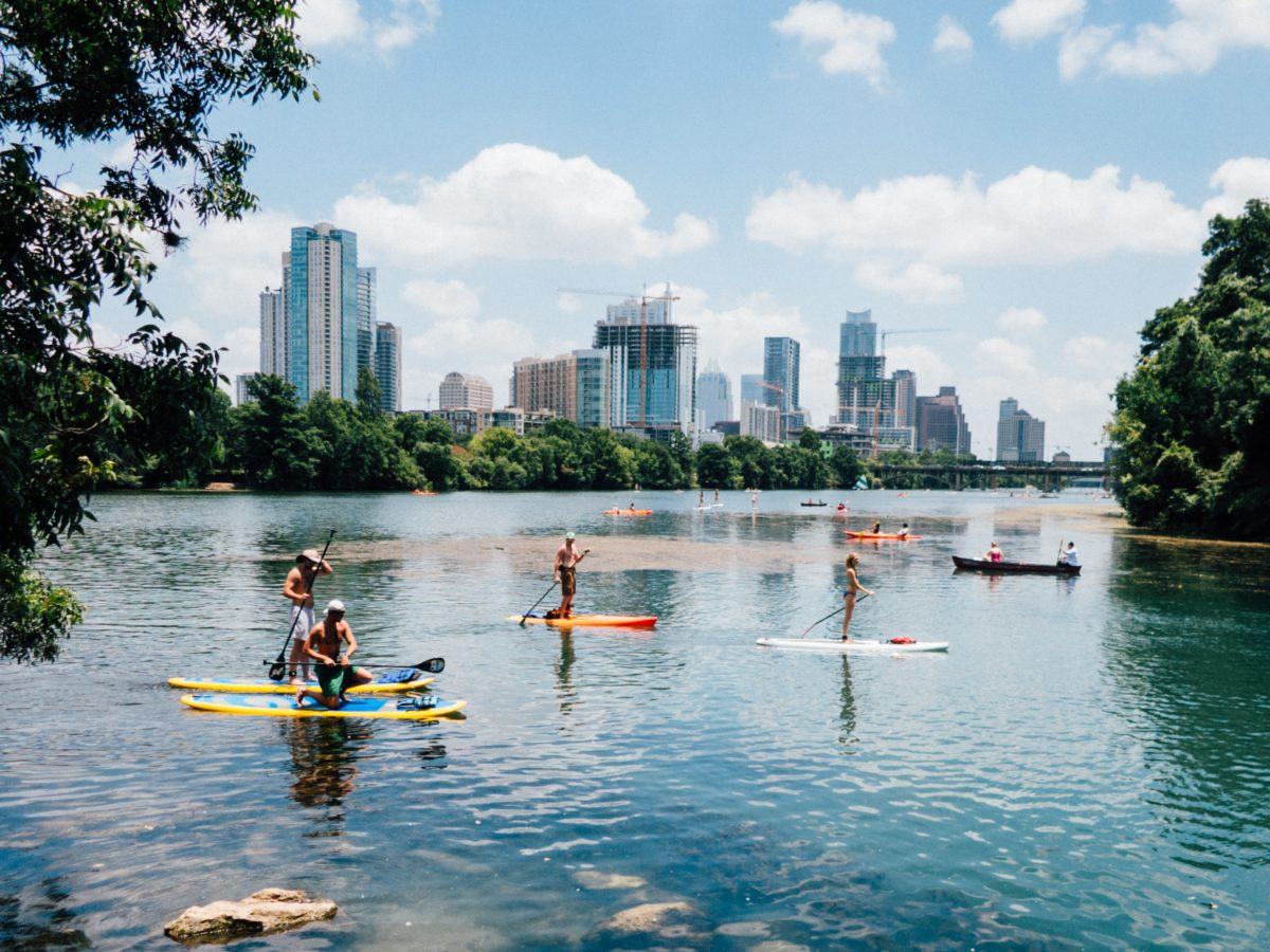 people kayaking, canoeing, and paddleboarding on a lake