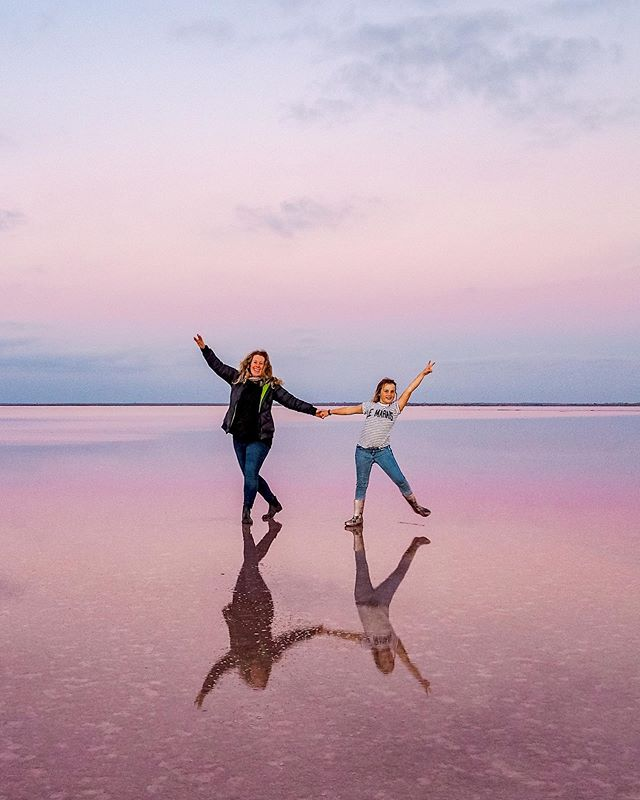 mother and daughter pose on a reflective natural surface at sunset