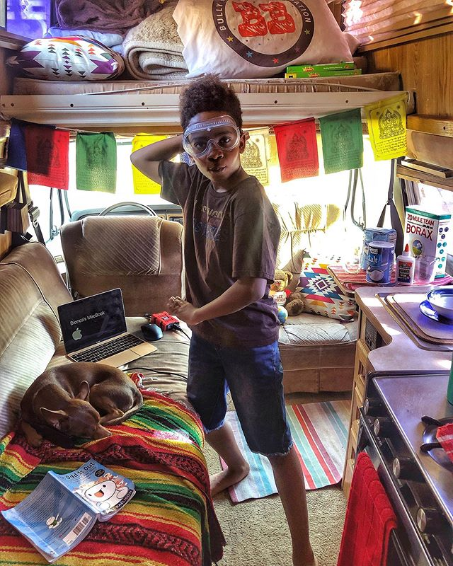 young boy with science goggles inside a camper van