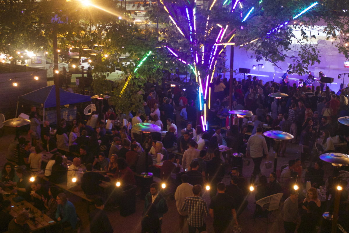a large crowd standing around a neon tree and a stage