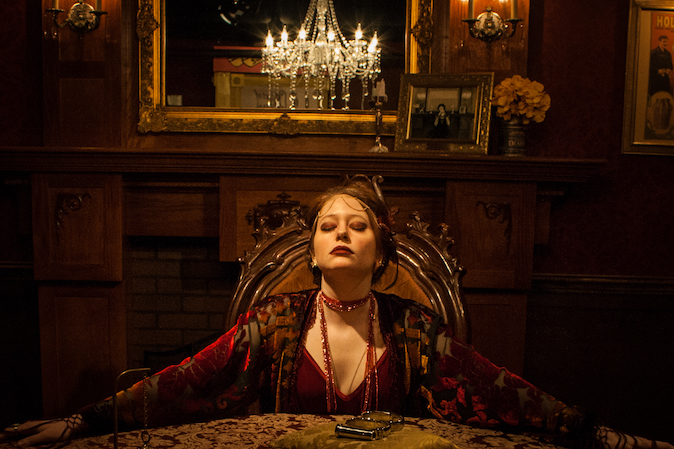 a woman sitting with her arms wrapped around the edges of a table in a mysterious room with a chandelier