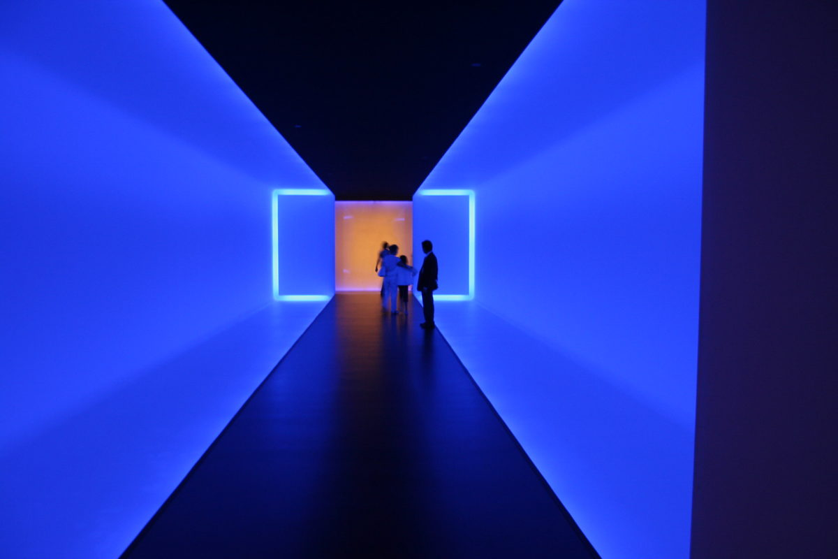 art installation in a hallway with blue neon lights