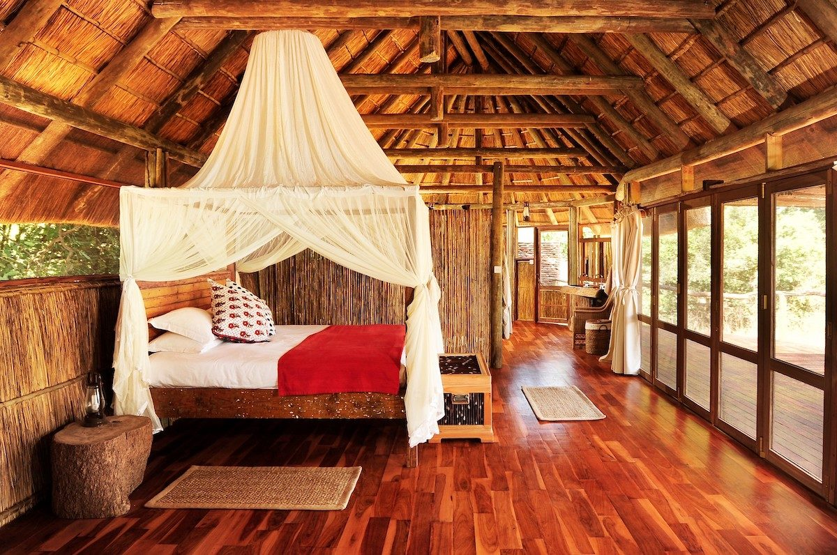 interior of a thatched-roof chalet with mosquito-netted bed