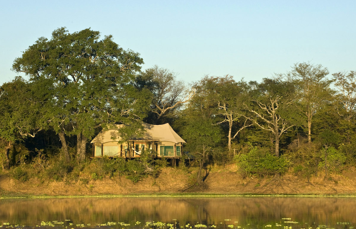 view of a bushcamp from opposite side of the river