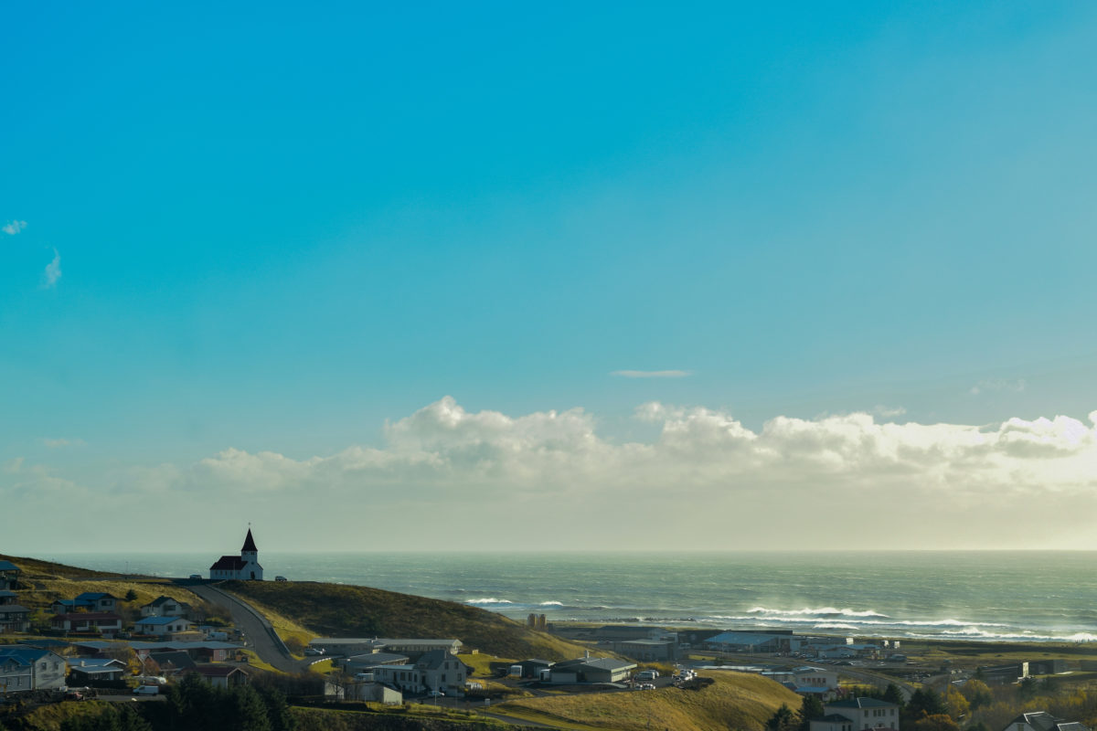 a church on a hill by the sea on a sunny day