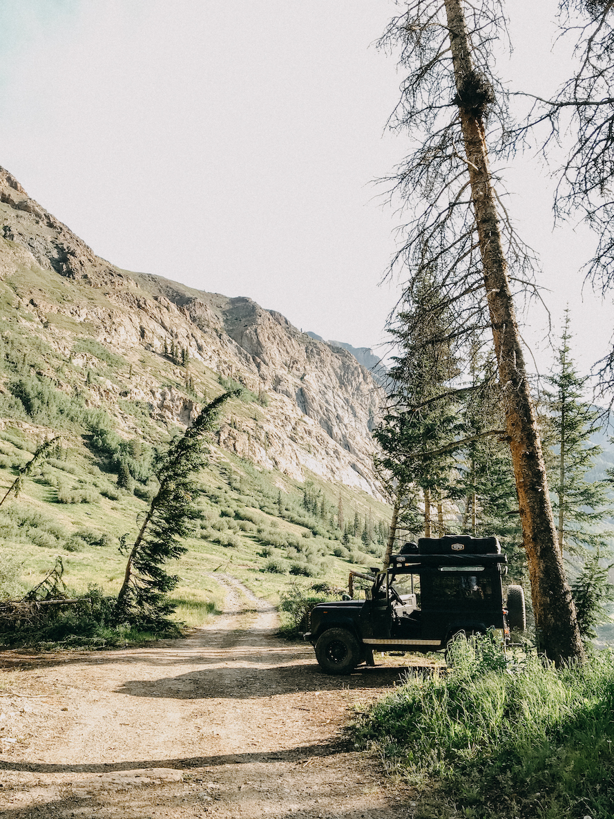 a jeep in the middle of a clearing by a mountainside