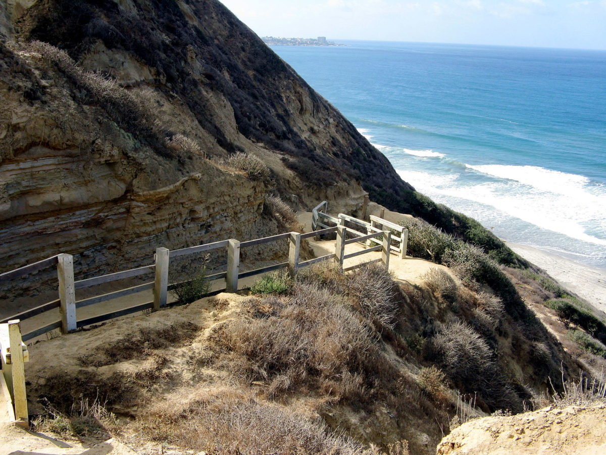 hiking trail on the side of a cliff near the beach