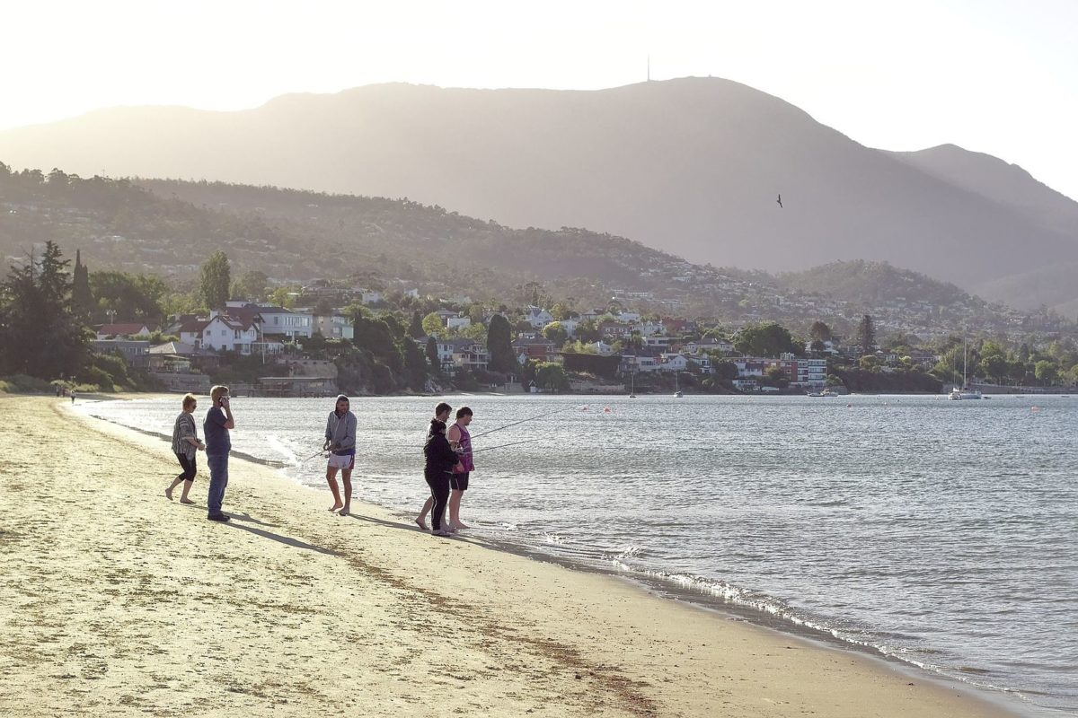 people walking along the shore of a beach with mountains in the background