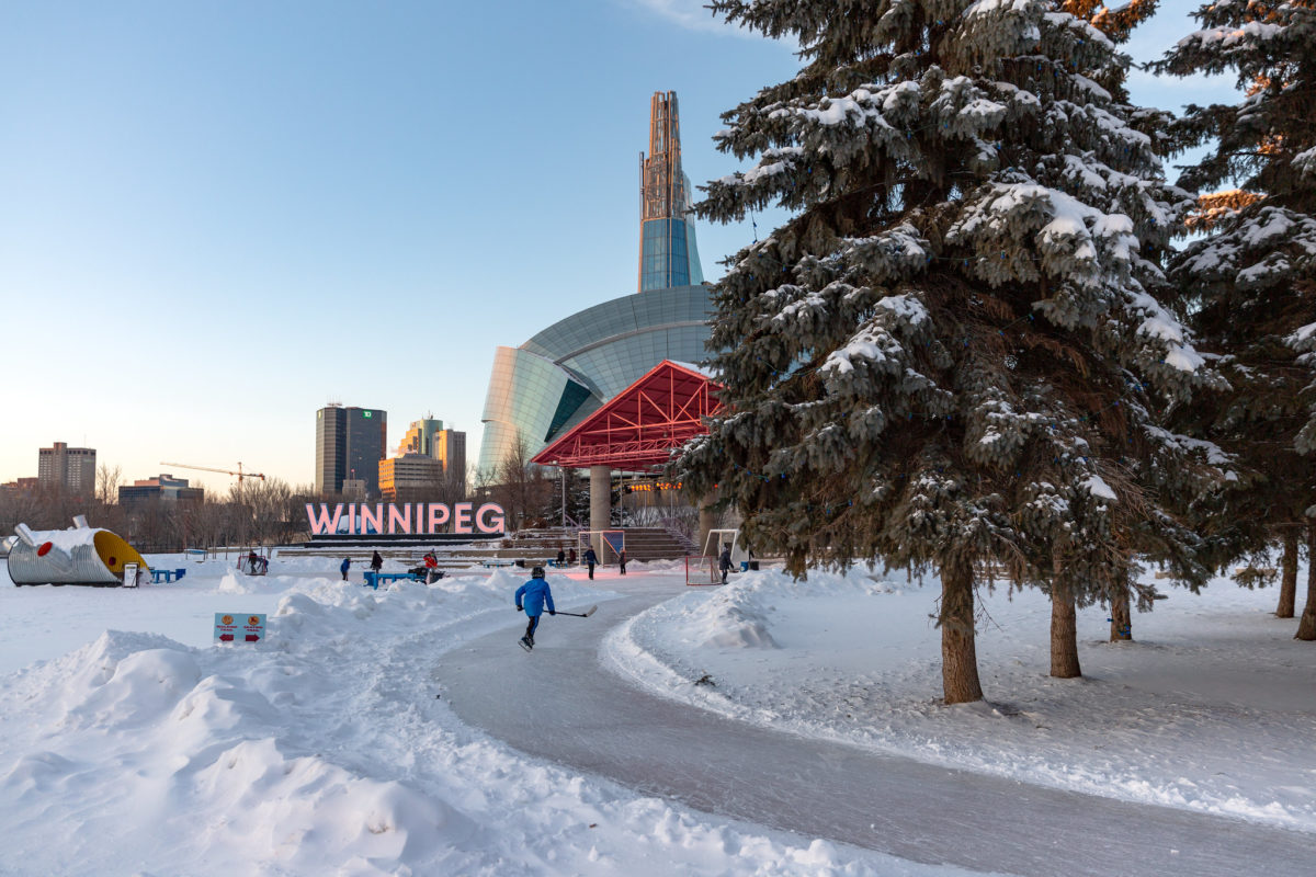 a person skates along a path in the snow with a large sign reading Winnipeg in the background
