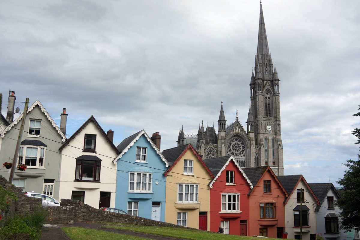colorful houses on a hill in front of a cathedral