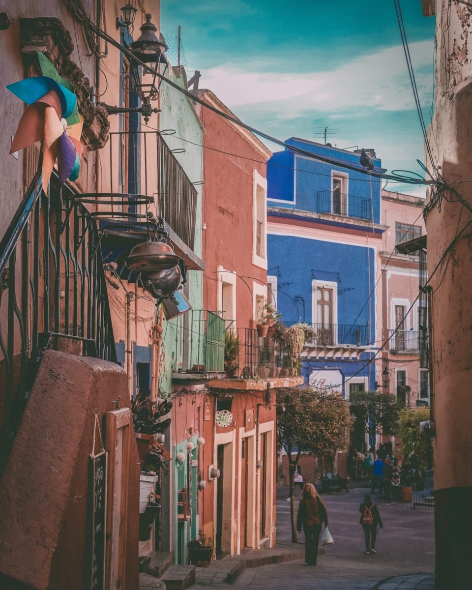 people walking on an old street with old colorful buildings
